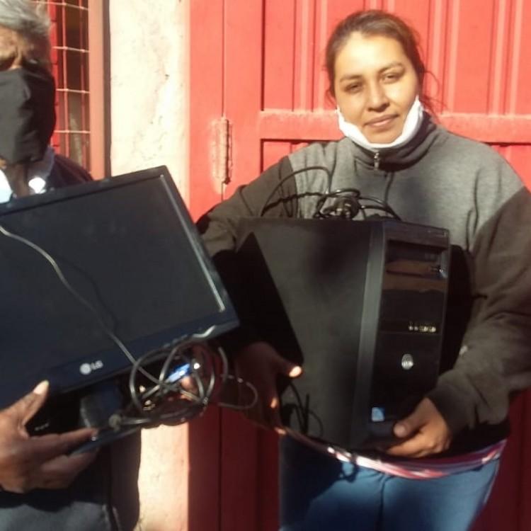 Eliana Carrizo junto a su padre reciben el equipo informático para continuar con sus estudios.